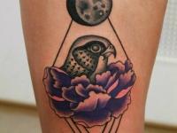 Татуировка птица в цветке на бедре