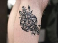 Татуировка абстрактного цветка с листиками на руке