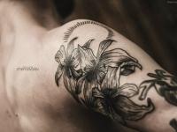 Татуировка в виде трех лилий на плече