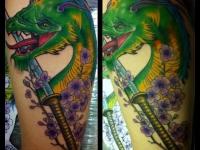 Татуировка голова дракона и меч