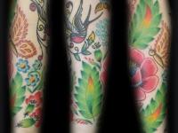 Татуировка ласточка и цветы на руке