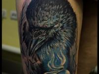 Татуировка голова птицы на бедре