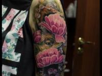 Татуировка взгляд из-за цветов на плече