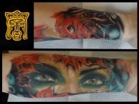 Татуировка глаза и кленовые листья на предплечье