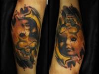 Татуировка лицо и череп на голени