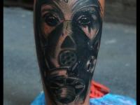 Татуировка лицо в железной маске на голени