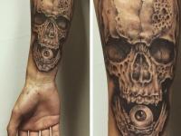Татуировка в виде черепа с глазом во рту на руке