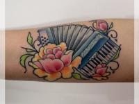 Татуировка аккордеон и роза на предплечье