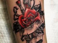 Татуировка на руке красная роза и кисти художника связанные лентой