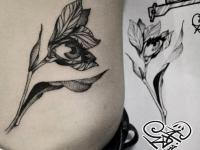 Татуировка цветка с глазом на боку