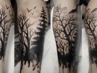 Татуировка темный лес и кружащиеся над ним вороны на руке