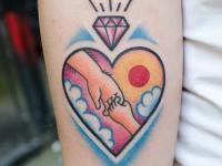 Тату сердце с изображением в нем рук и алмаз