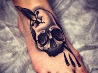Татуировка кинжал в черепе на ступне