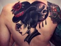 Татуировка  между лопаток женщина в шляпе и череп