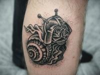 Татуировка улитка в маске на икре
