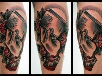 Татуировка рука с книгой на икре
