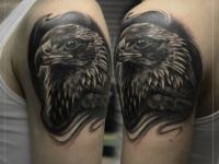 Тату голова грозного орла на плече мужчины