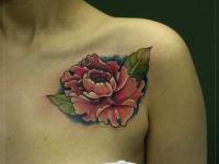 Татуировка красная роза на синем фоне возле плеча