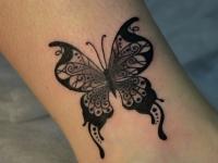Татуировка бабочка на голени