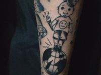 Татуировка в виде мальчика с факелом и в короне стоящего на мяче