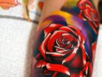 Татуировка в виде ярких разноцветных роз на внутренней части предплечья
