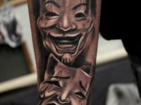 Татуировка веселой и грустной маски на руке