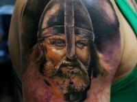 Татуировка в виде головы богатыря в шлеме на плече