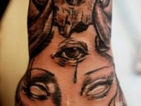 Татуировка череп и лицо на предплечье