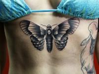 Татуировка бабочка под грудью девушки