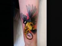 Татуировка синица с часами на предплечье