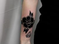 Татуировка черного цветка и кристала на руке
