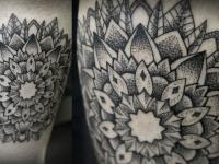 Татуировка узор в виде цветка из черных линий на руке