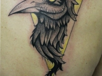 Татуировка головы птицы в желтом треугольнике