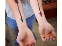 Татуировка стрела с цветным острием на предплечье