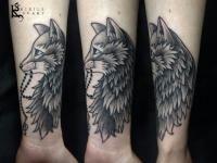 Татуировка кошка держащая в зубах четки на предплечье