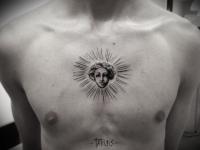 Татуировка лицо на груди