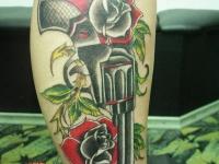Татуировка револьвер с розами на голени