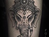 Татуировка головы слона с женскими глазами и сломанным бивнем на руке