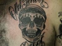 Татуировка череп с надписью на груди