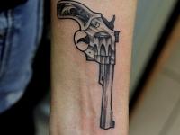 Татуировка револьвер на предплечье