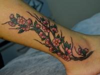 Татуировка ветка сакуры на щиколотке