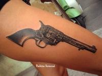 Татуировка револьвер на бедре