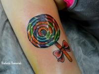 Татуировка леденец на палочке на плече