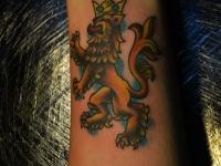 Татуировка лев в короне на предплечье
