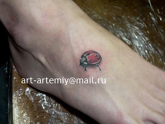 Татуировка божья коровка на ступне