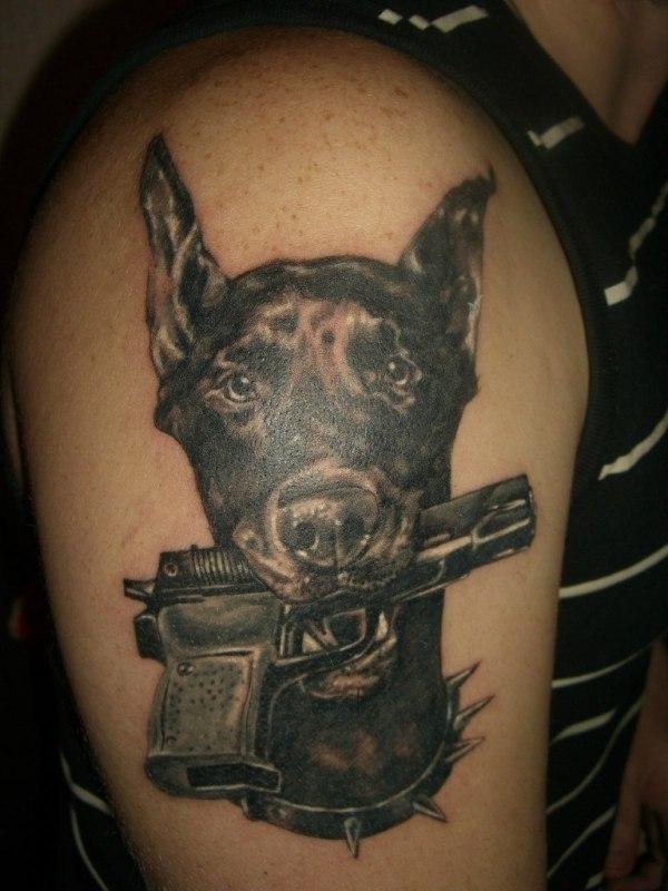 Татуировка собака с пистолетом в зубах на плече