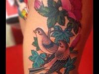 Татуировка птицы и цветок на колене