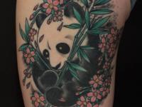 Тату панды с цветами на бедре девушки