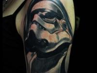 Татуировка голова в маске на плече