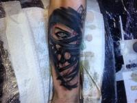 Татуировка лицо в повязке на руке